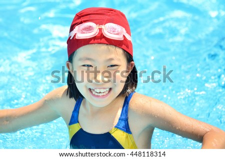 Girl playing in the swimming pool - stock photo