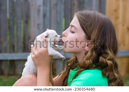 Girl playing kissing puppy chihuahua pet dog outdoor - stock photo