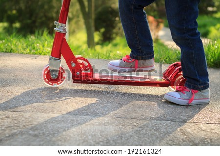 Girl playing mini scooter, kick scooter in park close-up - stock photo
