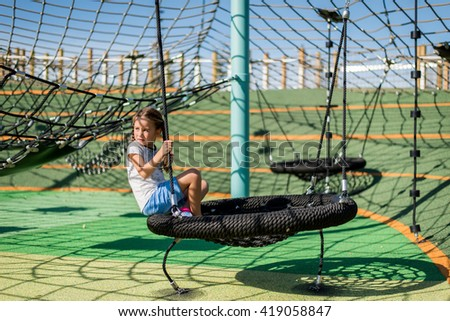 Girl playing on a climbing web.