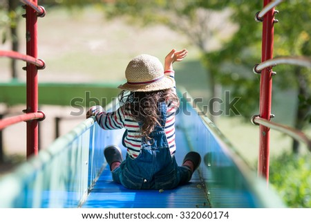 Girl playing on slide - stock photo