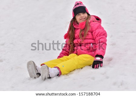Girl playing on snow - stock photo