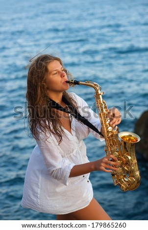 Girl playing saxophone sax at beach