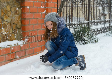 Girl playing snowballs in winter - stock photo