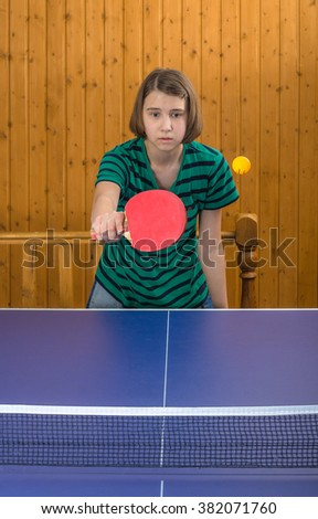 Girl playing table tennis with a cat - stock photo