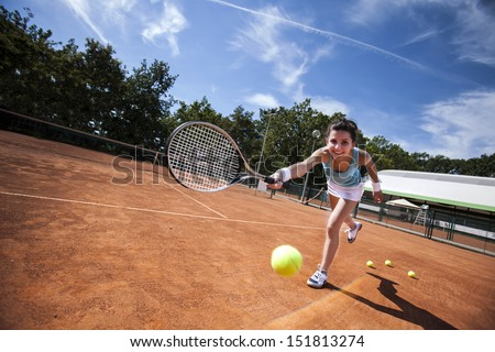 Girl playing tennis on the court on a beautiful sunny day - stock photo