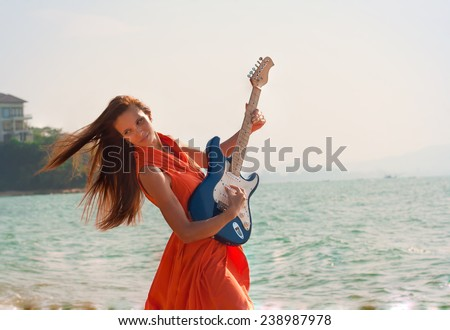 Girl playing the guitar. Beautiful girl with a guitar on the beach.