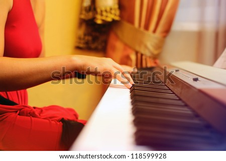 Girl playing the piano, hands closeup - stock photo