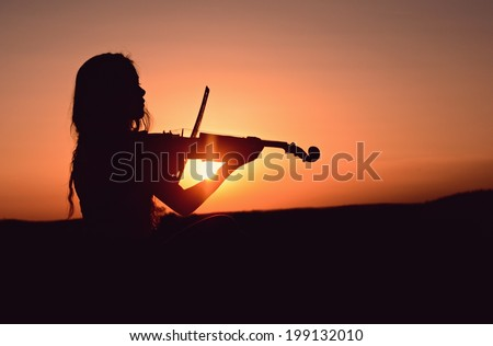 Girl playing the violin in the sunset