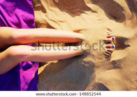 Girl playing to bury your feet in the sand on the beach - stock photo