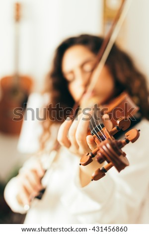 Girl playing violin. Young woman studying music alone at home in the living room with natural and soft light. Curly long and brunette hair, elegant dressed.