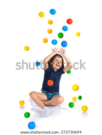 Girl playing while raining colored balls - stock photo