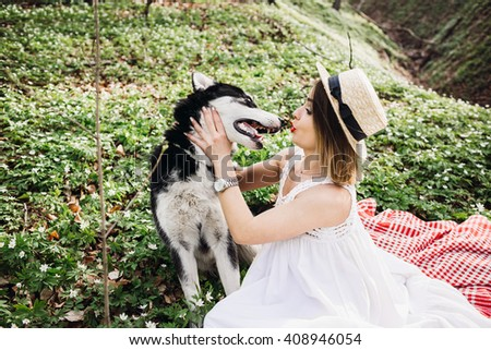 Girl playing with a dog in big forest - stock photo