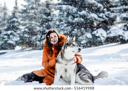 Girl playing with a dog in the park in winter.