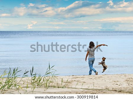 Girl playing with a dog on sandy beach of the Baltic Sea - stock photo