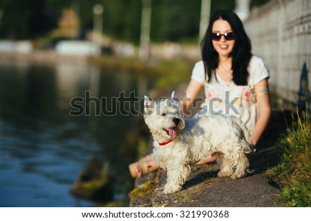 girl playing with a dog on the shore
