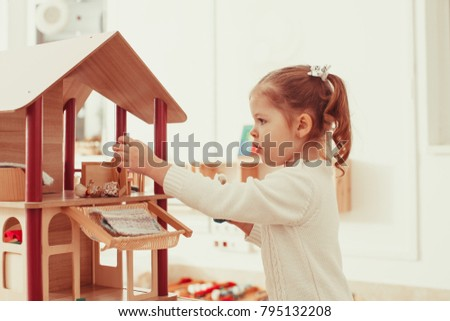 Girl playing with a dollhouse