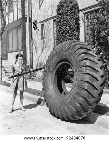 Girl playing with a huge tire and stick - stock photo