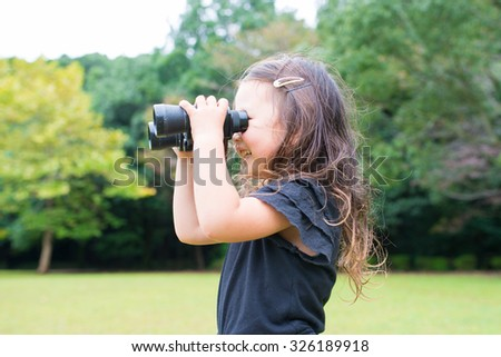 Girl playing with binoculars - stock photo
