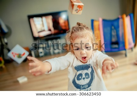 Girl playing with blocks and throws them forward - stock photo