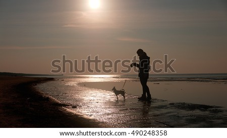 Girl playing with dog on a beach