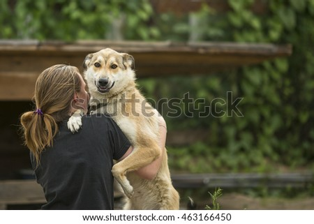 Girl playing with dog outdoors.