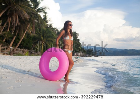girl playing with floating tube - stock photo