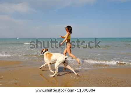 girl playing with her dog on the beach on a summer day