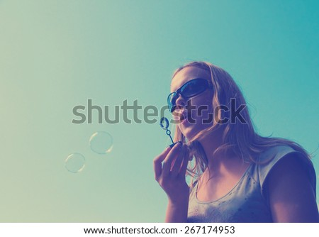 girl playing with lots of soap bubbles. Instagram style filtred image
