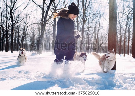 girl playing with siberian husky dog in snow - stock photo