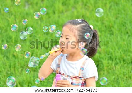 Girl playing with soap bubbles in the grassland