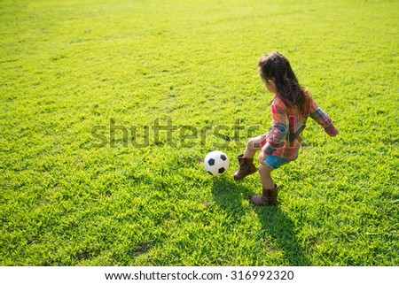 Girl playing with soccer ball - stock photo