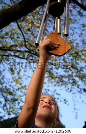 Girl playing with windchimes - stock photo