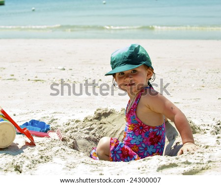Girl plays on the sand with the toys
