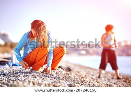girl plays on the sea beach at the early morning - stock photo