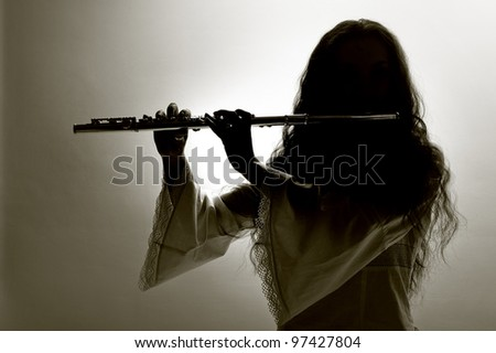 girl plays the flute on a grey background.silhouette - stock photo