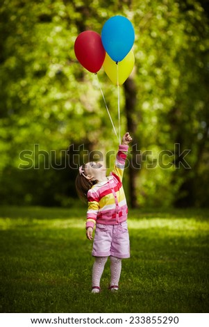girl plays with balloons in park - stock photo