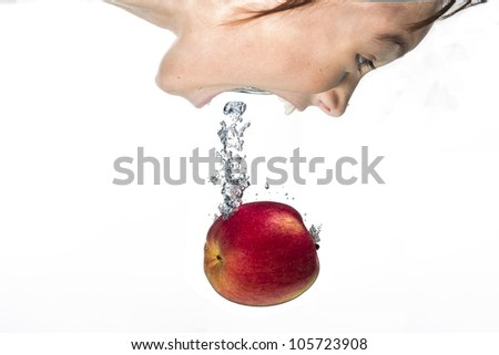 Girl plunges in for the apple. - stock photo
