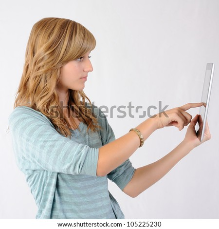 Girl Pointing at Tablet Computer. Teenage girl touching the screen of a tablet computer. Note: Not Isolated. - stock photo