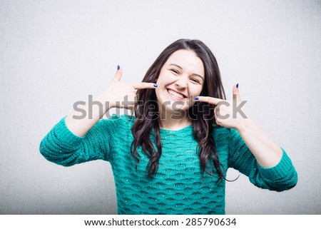 Girl pointing finger at his teeth with braces - stock photo