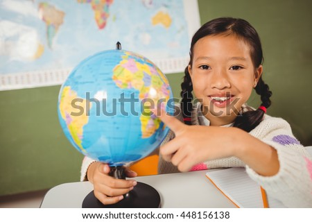 Girl pointing on globe at school