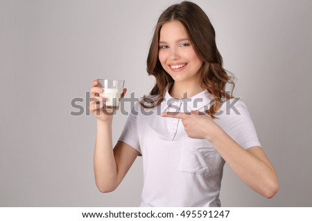 Girl points her finger at the glass of milk. Close up. White background