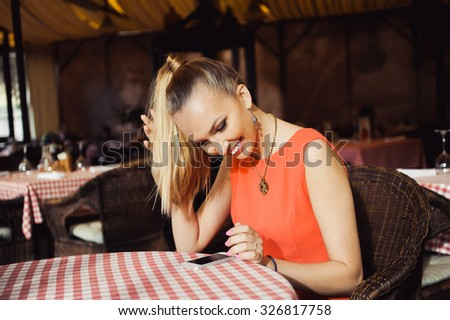girl portrait of a beautiful young blonde hair in a ponytail is sitting in the cafe lifestyle smiling with a phone in his hand posing - stock photo