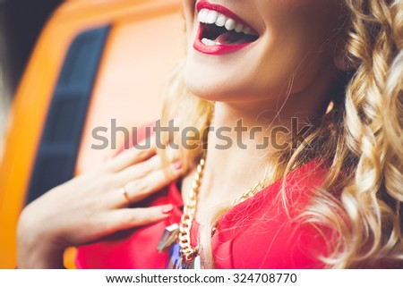 girl portrait of a beautiful young blonde  with red lips, bright makeup on orange background car smiling and posing lifestyle - stock photo