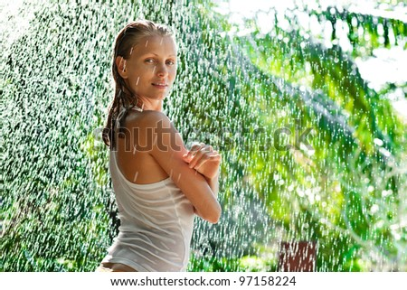 Girl portrait stay outside under in rain drops in tropical forest - stock photo