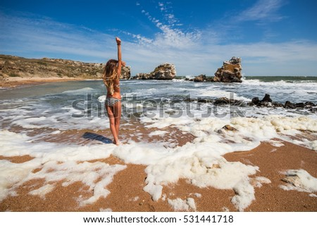 Girl poses in swimsuit on beah of sea and looks at beautiful sea, back view