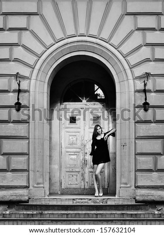 Girl poses near an old wooden door in the city, black and white photography