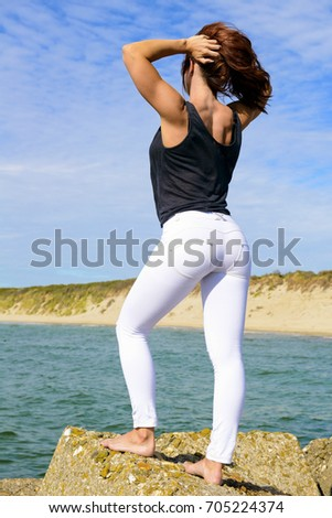 girl posing in a skinny push up jeans outside near the beach