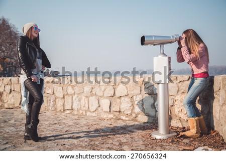 Girl posing in front of binoculars telescope - stock photo