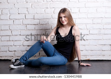 Girl posing in studio against a white brick wall